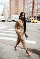 Black woman wearing suit with braids walking in the city